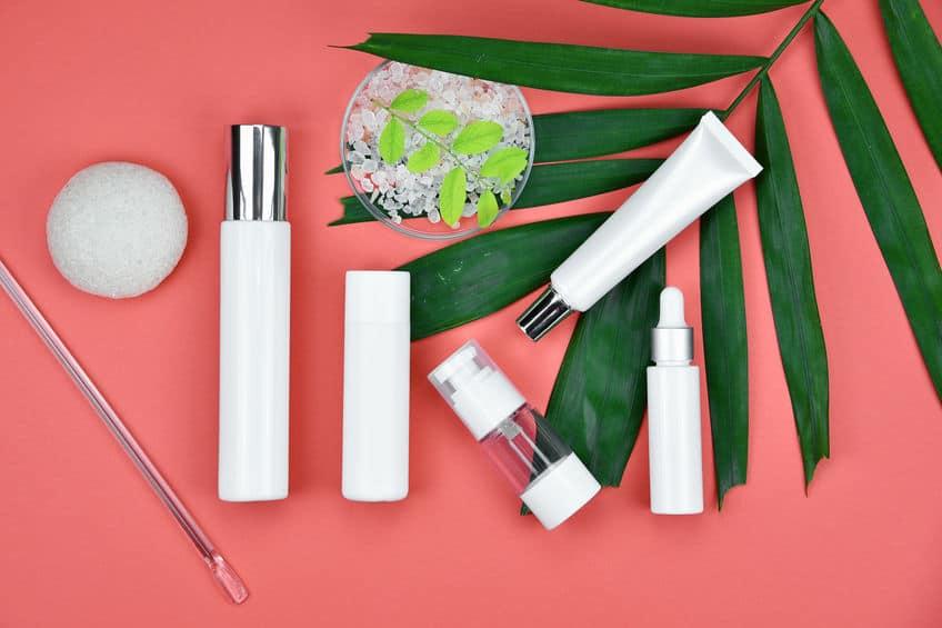Embalagens de cosmético com folhas ao fundo.