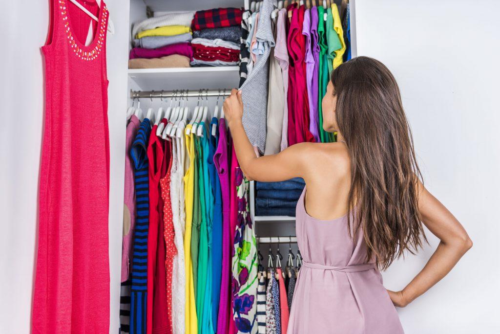 Mulher escolhendo roupa em guarda roupas.