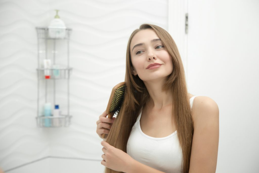 Jovem sorridente penteia os longos cabelos castanhos em um banheiro branco.