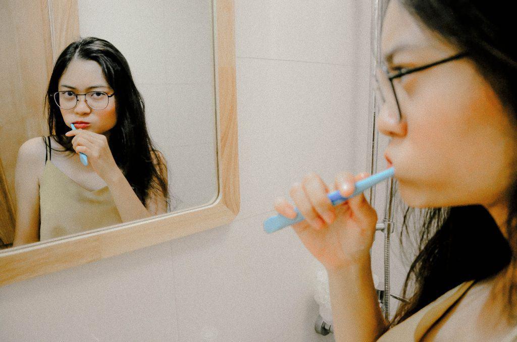 Uma garota está se olhando no espelho enquanto escova os dentes.