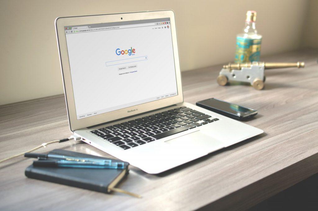 Notebook na mesa, com tela aberta na pagina do Google.