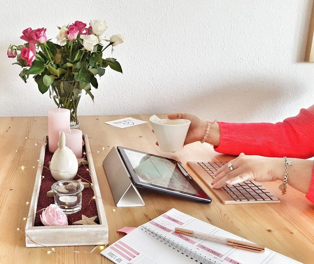 Mulher digitando no teclado, enquanto observa o tablet.
