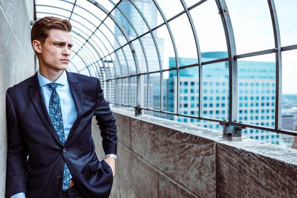 Um homem vestindo um blazer está em pé, encostado contra uma parede, no que parece ser o topo de um prédio.