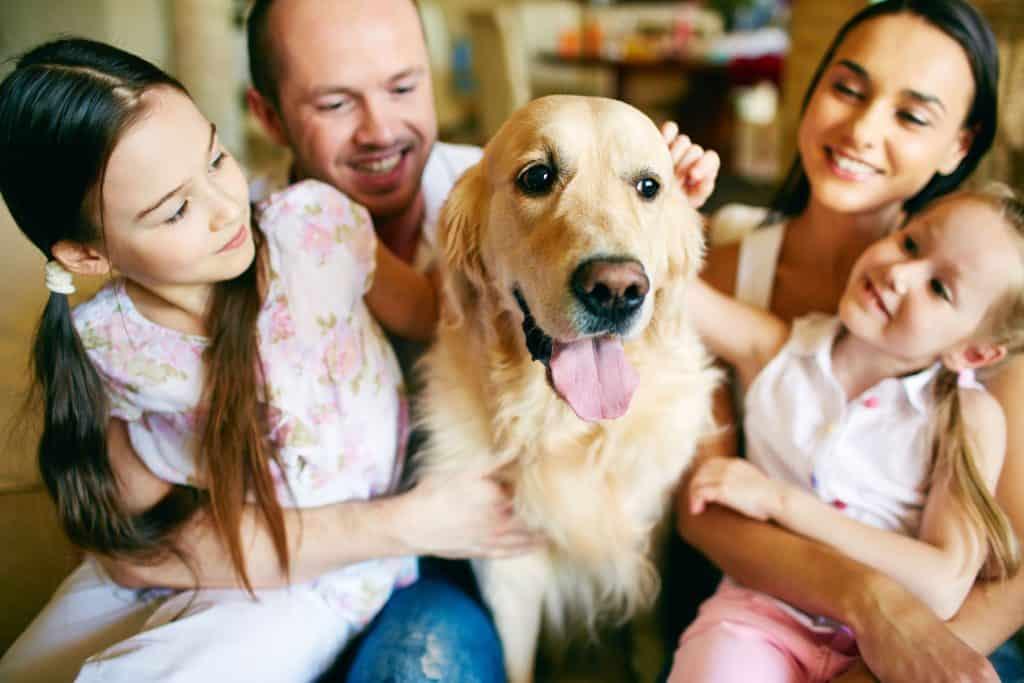 Imagem de uma família feliz em frente sua casa.
