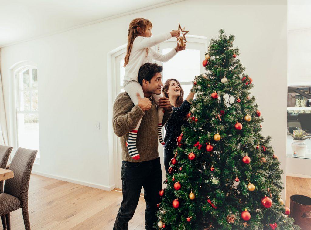 Família montando árvore grande de natal.