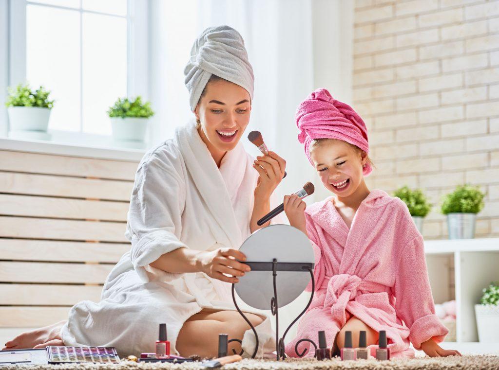 Mãe e filha fazendo maquiagem.