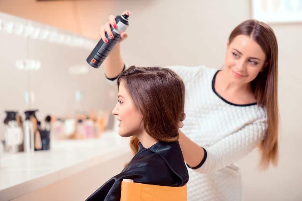 Na foto uma mulher aplicando spray no cabelo de outra.