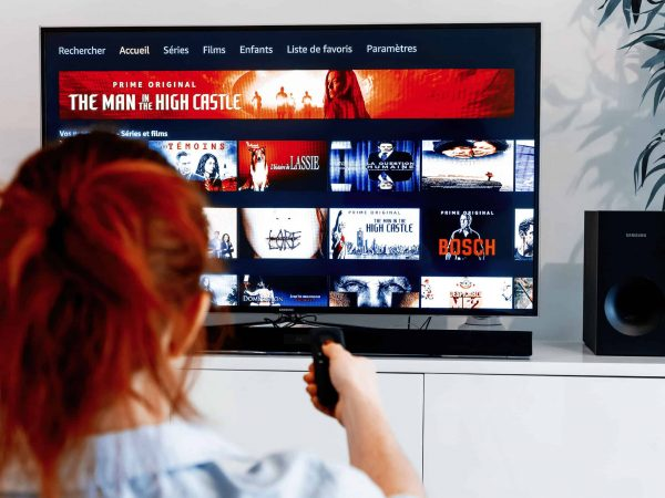 mulher assistindo tv com controle remoto na mão.