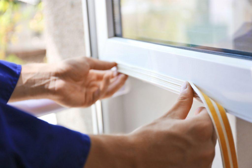 Mãos fixando vedação em porta com fita dupla face.