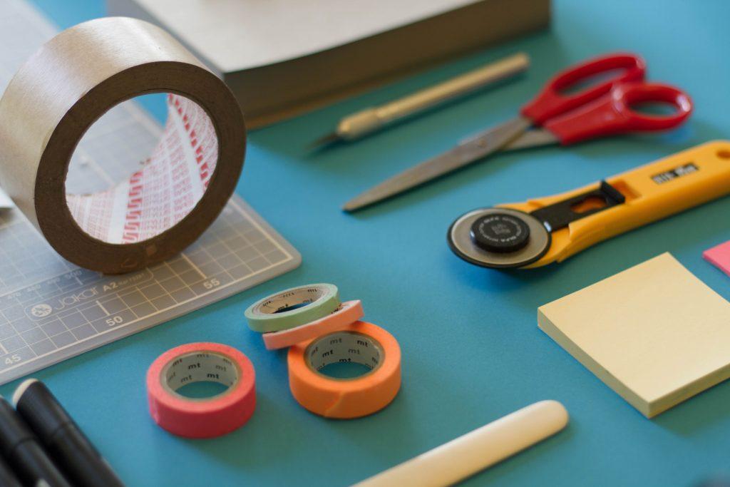 Imagem mostra um rolos de fita crepe de várias cores e vários tamanhos numa mesa repleta de itens de escritório.