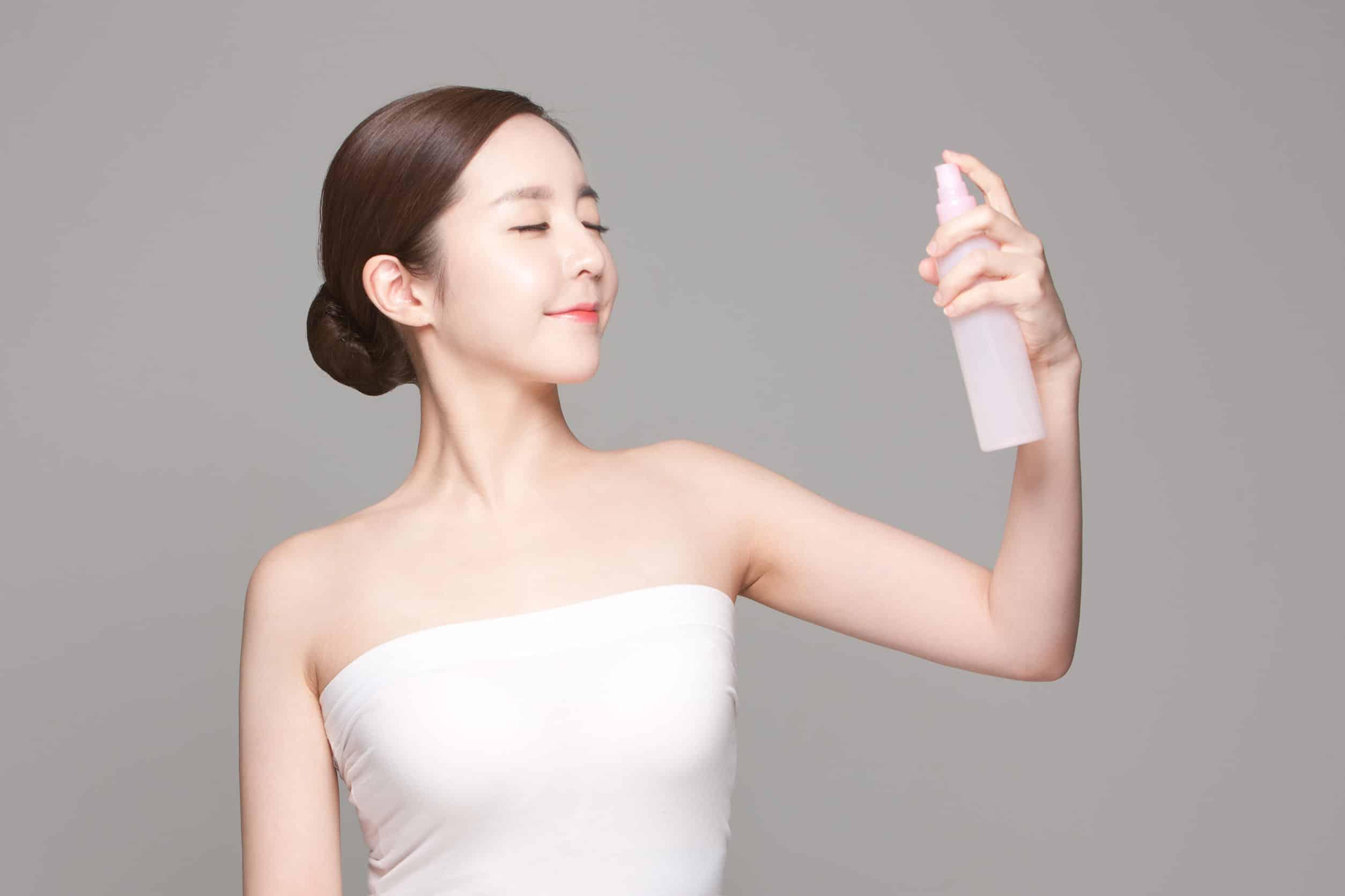 Foto de uma mulher oriental de blusa branca tomara que caia e cabelo preso em um coque, de olhos fechados e apontando um produto em spray para o seu rosto.