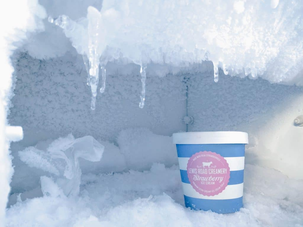 Congelador de geladeira com gelo acumulado e pote de sorvete.