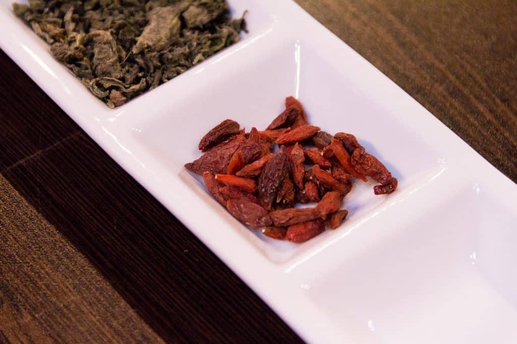 Imagem mostra uma porção de goji berries desidratados e empratados como petiscos sobre uma superfície de madeira.