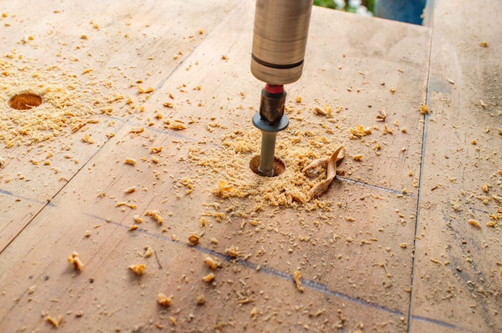 Ponta de furadeira perfurando madeira.