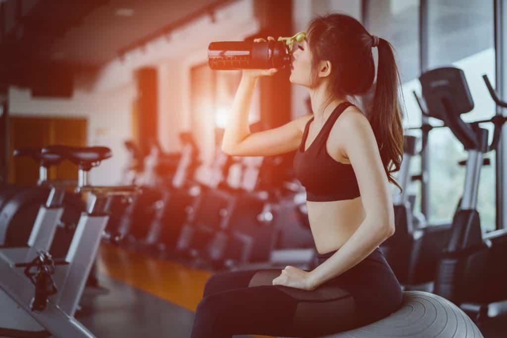 Imagem de uma garota sentada em uma bola de pilates dentro de uma academia.
