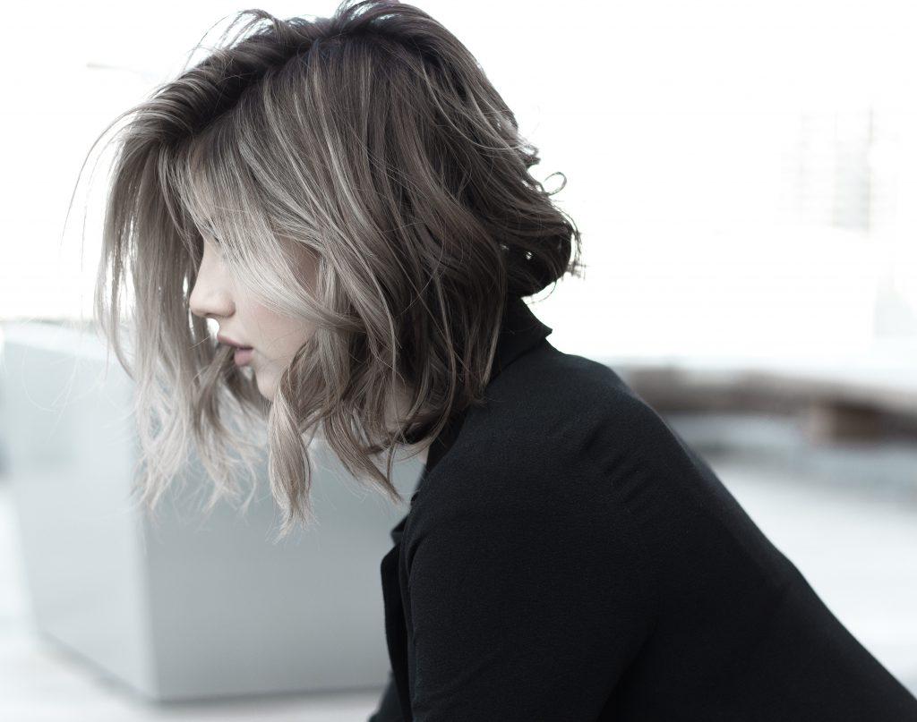 Na foto uma mulher loira de cabelo curto enrolado sentada de perfil.