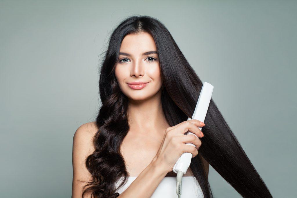Imagem de uma garota utilizando chapinha nos cabelos.