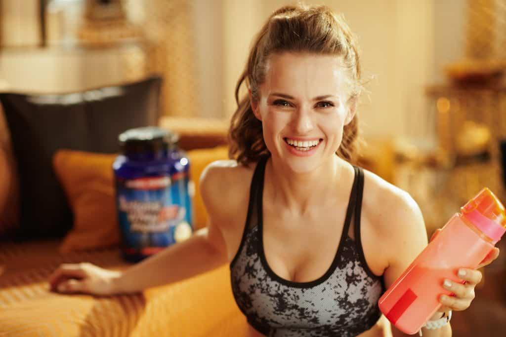Imagem mostra uma mulher numa sala, sorrindo para a câmera enquanto segura uma garrafa própria para shakes. Ao seu lado, esta um grande pote de suplemento, desfocado e em segundo plano no quadro.