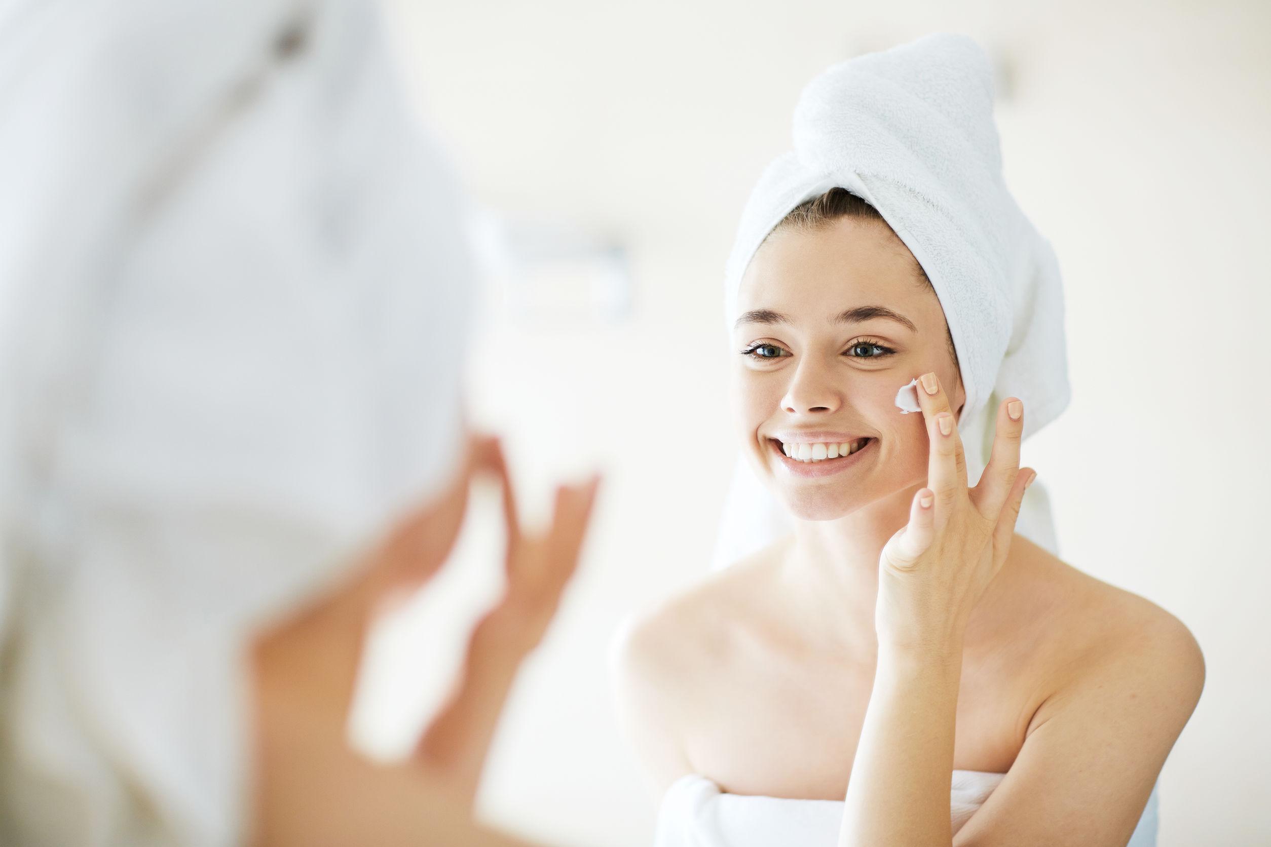 Na foto uma mulher de toalha aplicando creme no rosto.