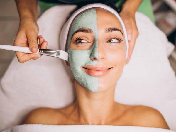 Esteticista aplica máscara facial verde no rosto de uma mulher sorridente.