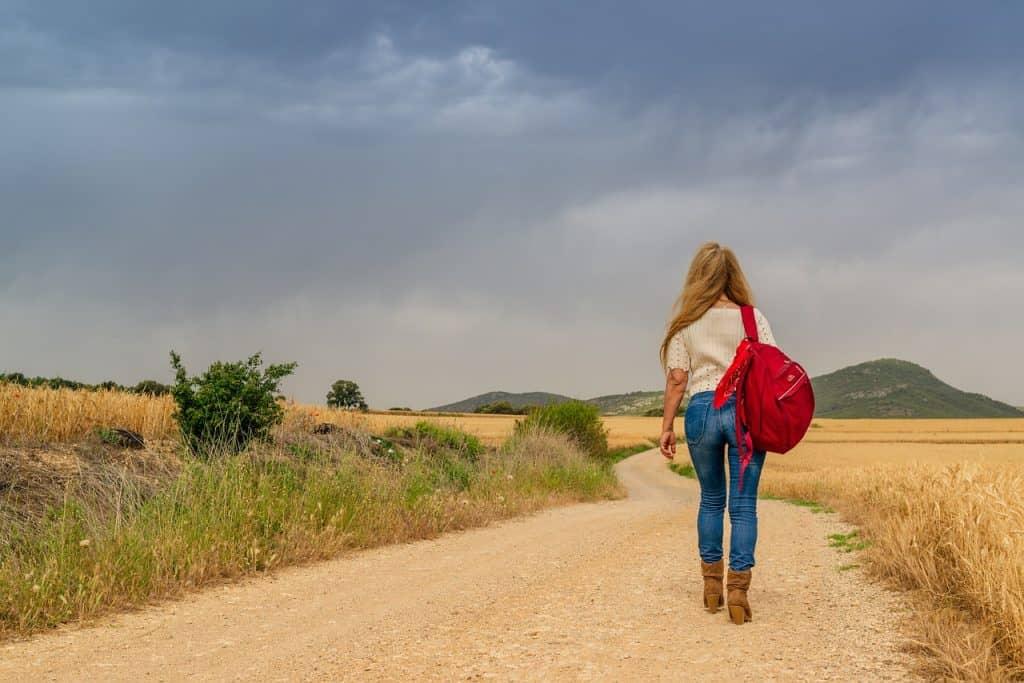 Uma mulher caminhando em uma estrada com uma mochila pendurada em um dos ombros.