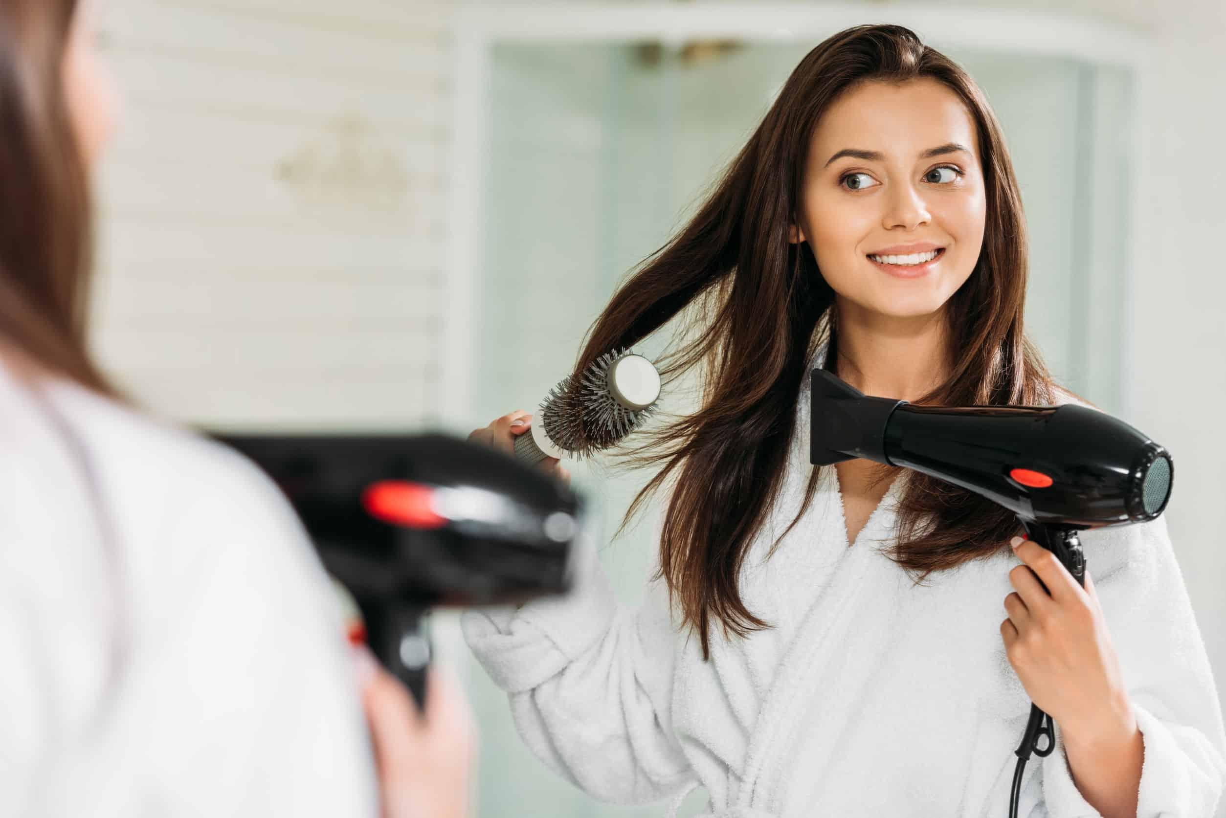 Na foto uma mulher dentro de um banheiro secando seu cabelo.