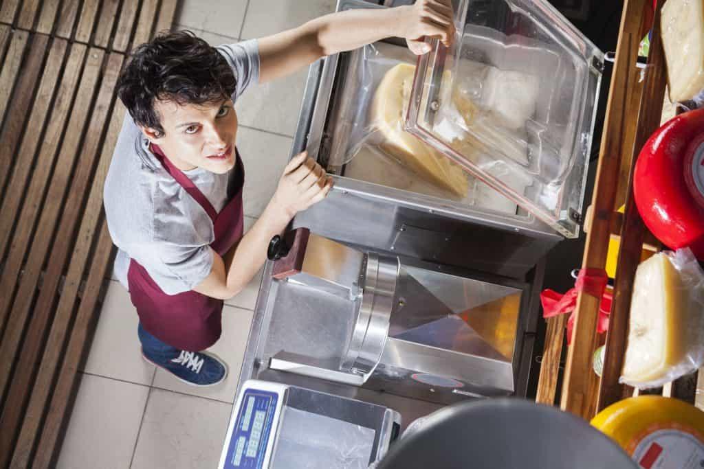 Funcionário de mercearia embala grandes peças de queijo em seladora a vácuo.