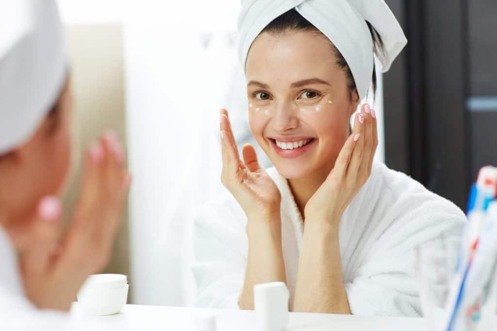 Mulher vestida com roupão branco e toalha branca na cabeça aplica creme na área dos olhos sorrindo no espelho.