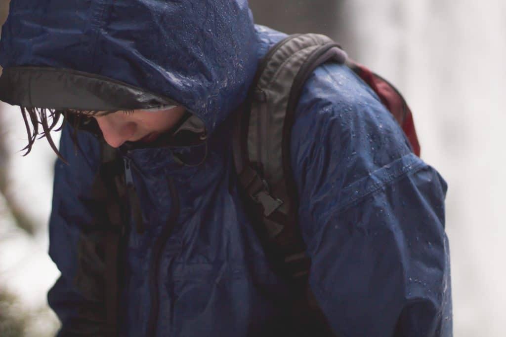 Pessoa com capa de chuva e mochila.