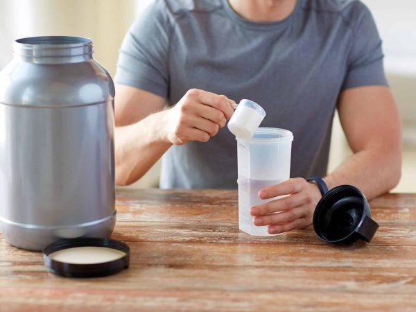 Imagem mostra um homem derramando o pó de um suplemento num copo de academia, apoiado numa mesa de madeira. Na mesma mesa, há o pote do suplemento, com a tampa aberta.