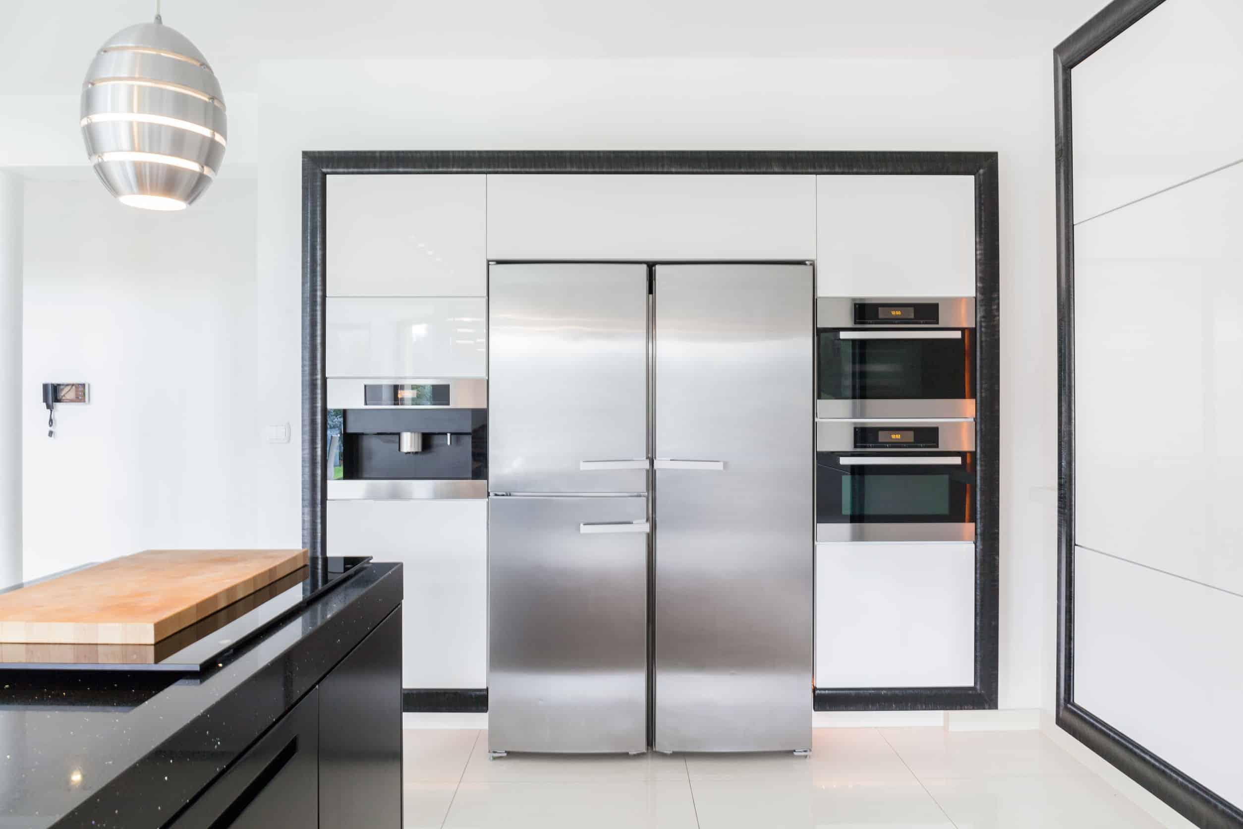 Cozinha branca e preta com geladeira na cor inox do tipo Side by Side.