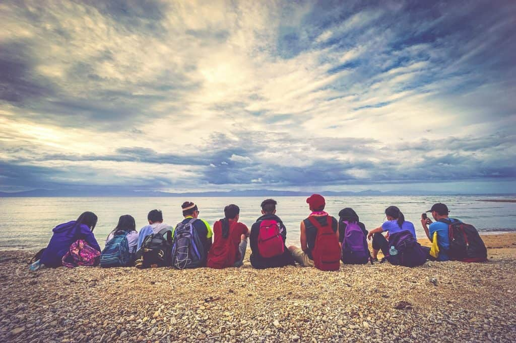 Um grupo de jovens com mochilas nas costas sentados na frente do mar.