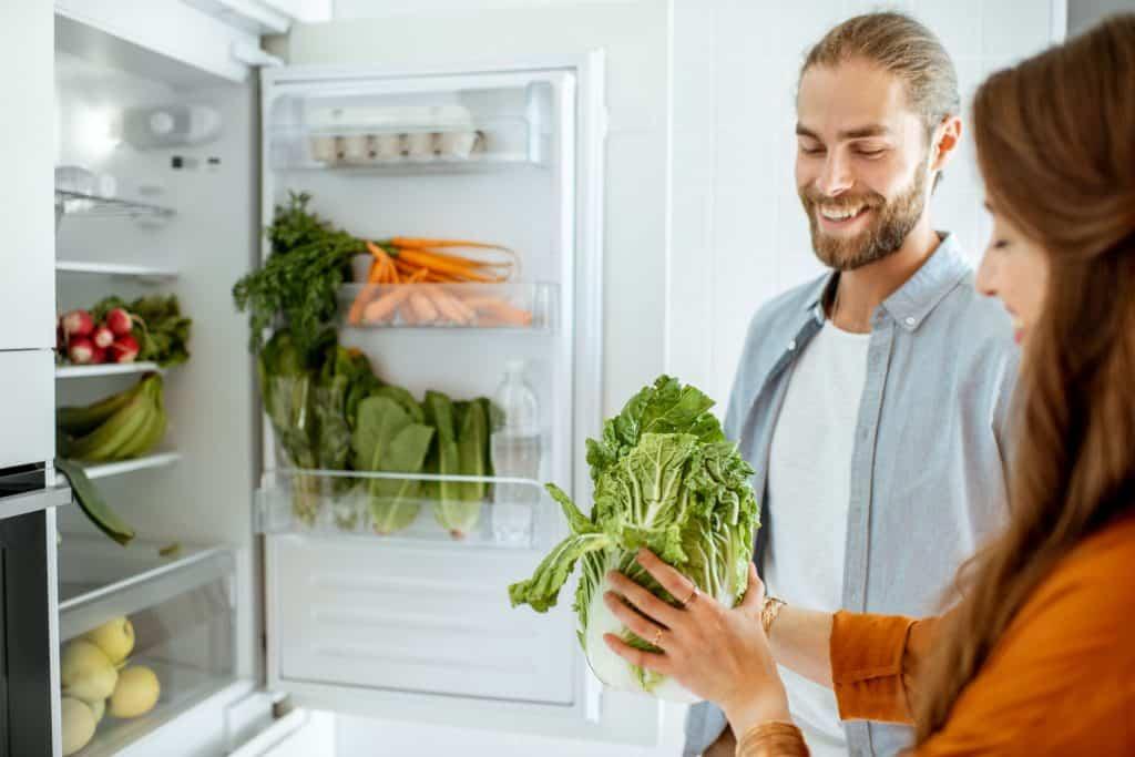 Casal guardando verduras na geladeira.