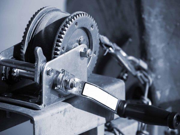 Imagem mostra um guincho manual de manivela.