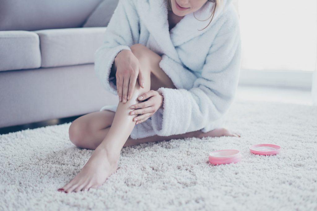 Foto mostra uma mulher passando hidratante nas pernas.
