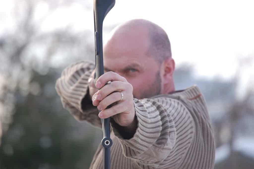 Homem mirando com arco e flecha.
