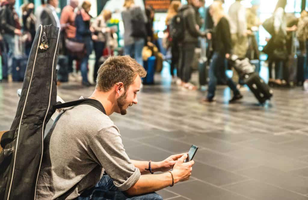Em uma estação de metrô um homem está sentado em um banco mexendo no celular. Ele tem uma capa para violão nas costas.