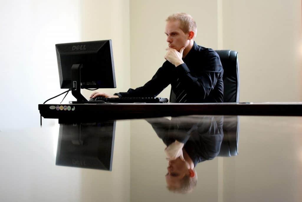 Um homem com camisa longa mexe no mouse do computador e olha ao monitor em uma sala com parede branca.