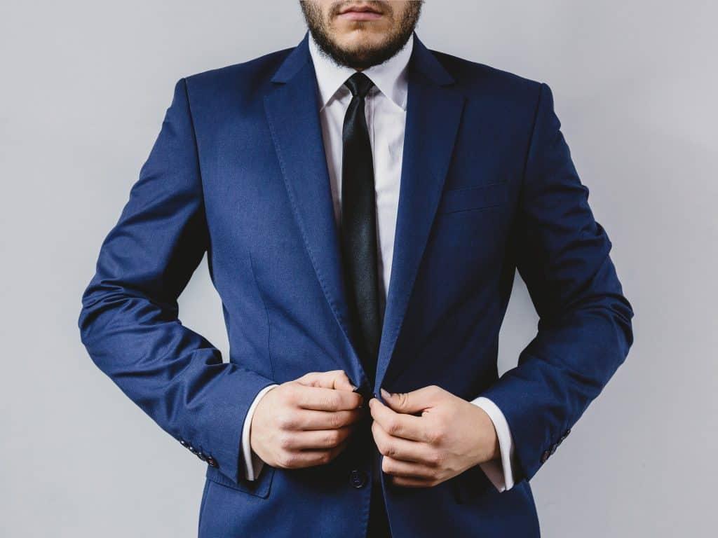 Um homem está abotoando seu blazer, que é de cor azul.
