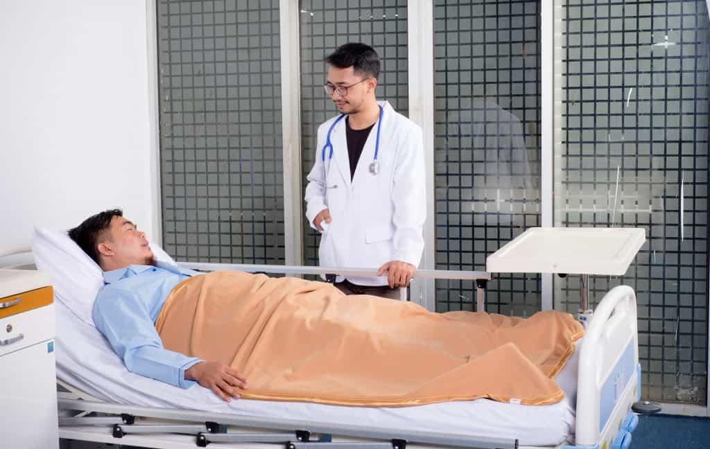Paciente na maca conversando com médico em pé.