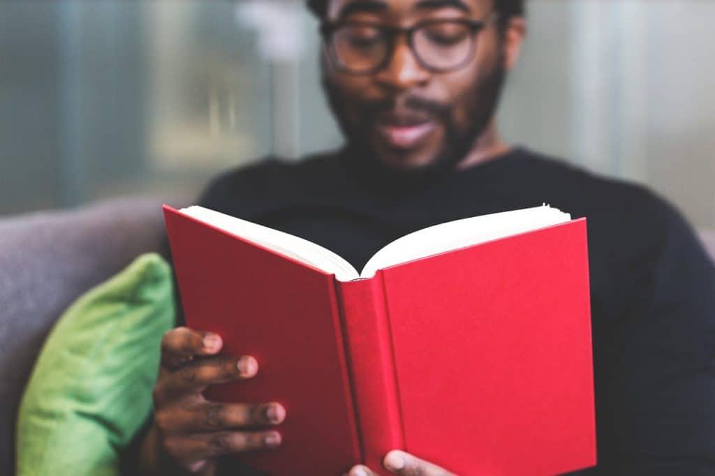 Um homem sentado no sofá, vestindo uma blusa preta e usando um óculos, está segundo e lendo um livro de capa vermelha.