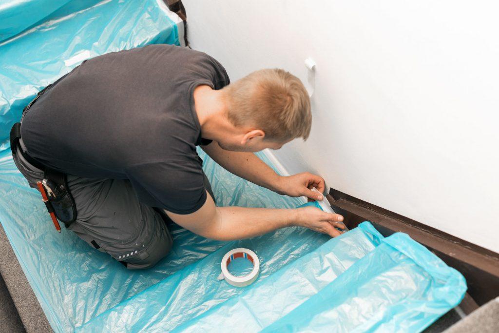 Imagem mostra um homem ajoelhado numa escada e fixando uma capa de plástico com uma fita crepe, cujo rolo repousa num dos degraus à sua frente.
