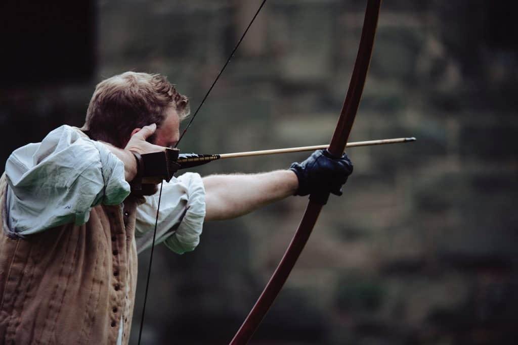 Homem mirando com arco e flecha de luvas.