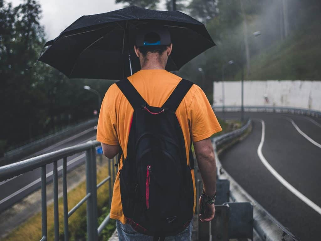 Homem com guarda-chuva e mochila na rua.