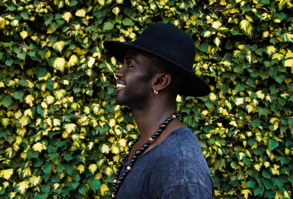Imagem mostra um homem posando de perfil, usando um chapéu e um longo colar, usando um brinco de argola dourado em sua orelha esquerda.
