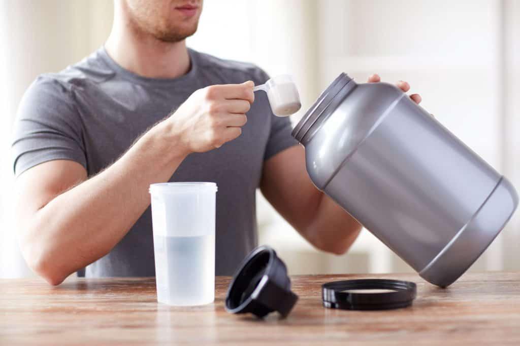 Imagem de um homem pegando suplemento do pote com um dosador.