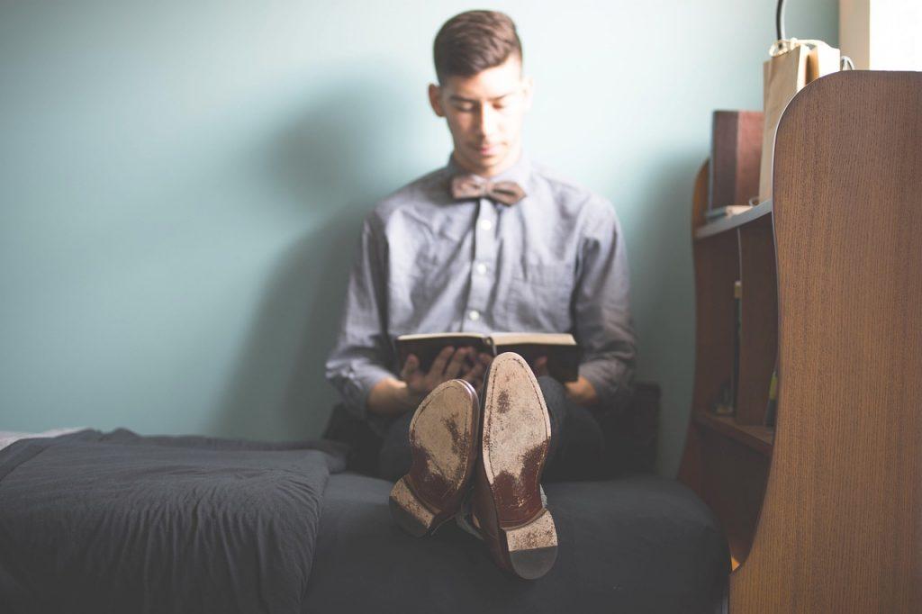 Imagem mostra um homem sentado em uma cama e lendo um livro.