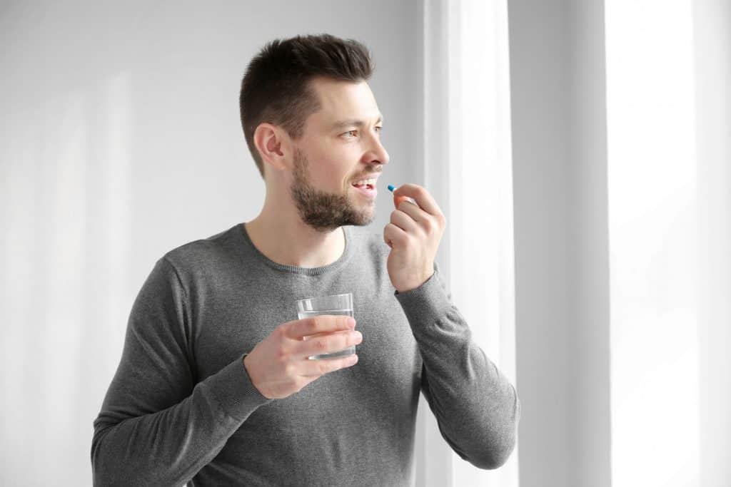 Homem segurando comprimido e copo de água.
