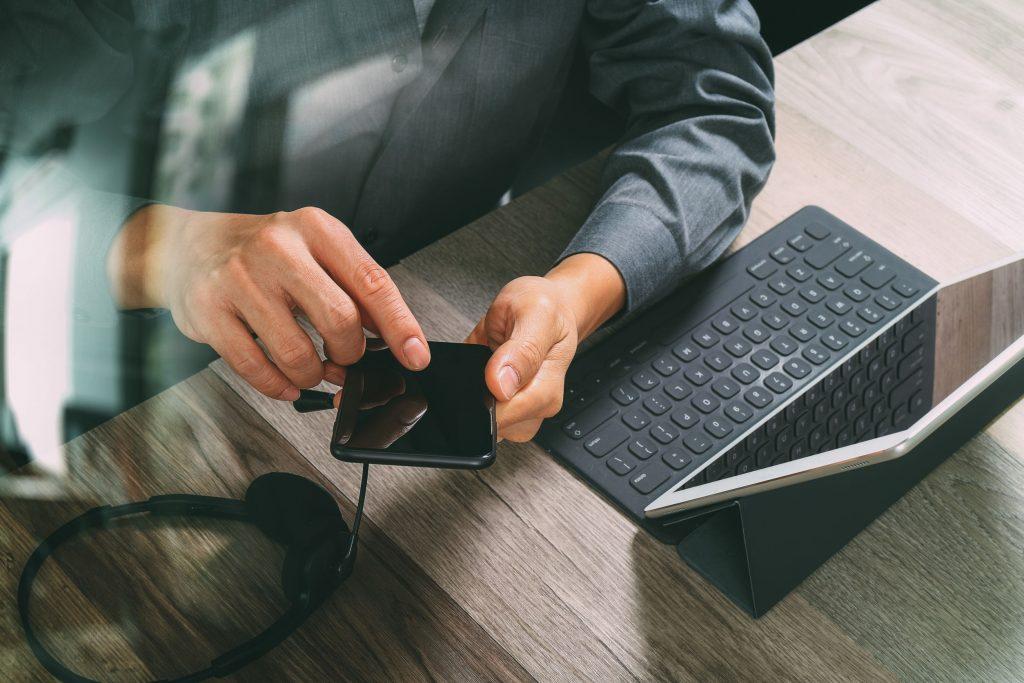 Homem com smartphone e tablet com teclado a frente.