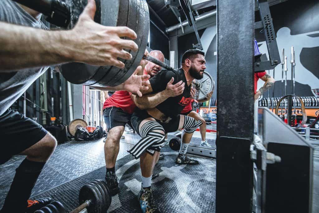 Homem carregando peso em academia.